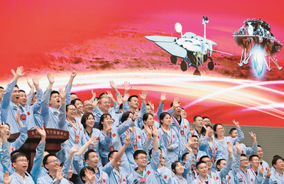 Aerospace scientists celebrate the landing of China's first probe on Mars at the Beijing Aerospace Control Center, May 15, 2021.