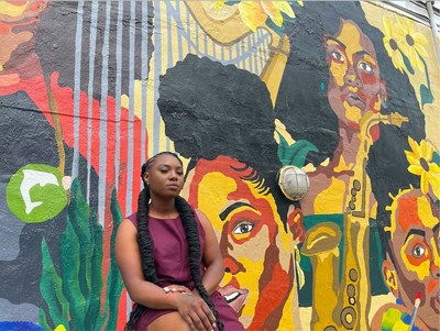 Muralist Erica Chisolm poses with Shine Different Mural Commissioned by Creme of Nature #ShineDifferent