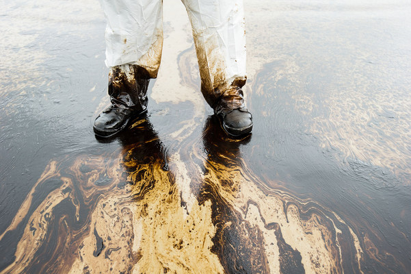 Clean up worker stands in the Orange County oil spill