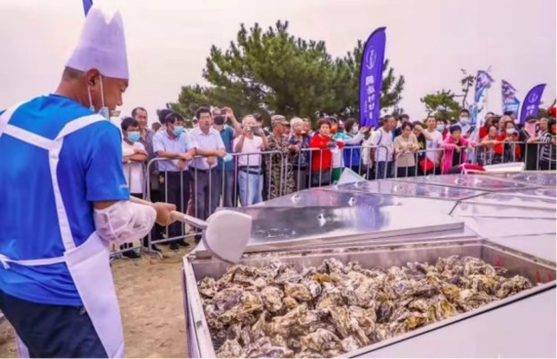Tourists enjoy the Super Oyster Feast (PRNewsfoto/The People's Government of Rushan)